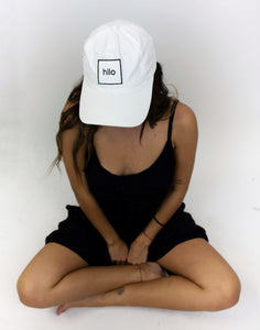"The model in this photo is wearing a black outfit and is wearing a white cotton baseball cap, with the square ""Hilo"" logo embroidered on the front in black thread."