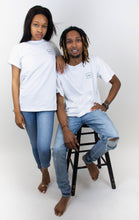 "Load image into Gallery viewer, photo shows two people wearing white cotton T-shirts, the T-shirts have a small ""hilo"" square logo on the right breast of the shirt."