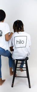 "Photo shows a model with his back facing us wearing a white cotton T-shirt that has a large ""hilo"" square logo centered on the back."