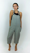 Load image into Gallery viewer, There's a model wearing black and white overalls. The overalls have two straps that are on either shoulder that can be adjusted by the two black buttons on the end of the straps. The overalls hit the models mid calves, and the overalls from a distance look grey due to the small black and white pattern that is on the fabric.