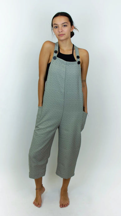 There's a model wearing black and white overalls. The overalls have two straps that are on either shoulder that can be adjusted by the two black buttons on the end of the straps. The overalls hit the models mid calves, and the overalls from a distance look grey due to the small black and white pattern that is on the fabric.
