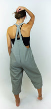 Load image into Gallery viewer, The model in this photo has her back facing us and is wearing pair of overalls that are black and white. The overalls from afar appear to be grey because of how small the black and white pattern is on the fabric. There are two straps that go over the shoulders of the overalls that form an X on the models back. These straps can be adjusted with two buttons.