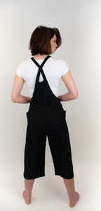 This image is of a girl whose back is facing us. She is wearing a white t-shirt under the black overalls she is wearing. The overalls are black and made of a soft linen, the overall pants hit her mid-calf, and the straps that connect to the front of the overalls make an X shape on her back.