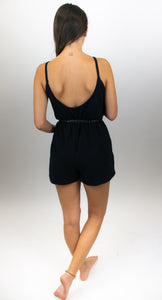 This photo shows a model standing with her back facing us and wearing black shorts romper that reaches her mid-thigh. The back of this romper is cut very low.