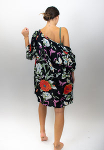 This photo shows a model with her back facing us with large printed orange flowers as well as white flowers, and small purple butterflies. The background on the kimono is black and the accent colors are orange and white and lilac. The kimono is boxy and reaches just below the crotch on the model.