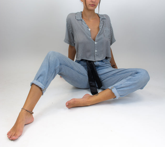 This photo shows a model sitting on the floor with a pair of jeans and a button up shirt on. The button up shirt is cropped and has a black and white pin stripe pattern on it, the buttons are white and the top itself is flowy and has a front pocket on the upper left side of the chest.