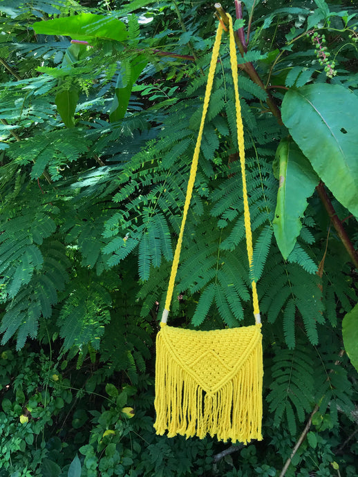 Photo shows a sunshine yellow cross body bag hanging from a tree branch