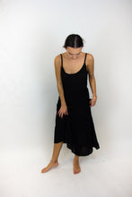 Load image into Gallery viewer, This photo shows a long and lightweight dress that is black and spaghetti strapped. The model is twirling it to show how it moves.
