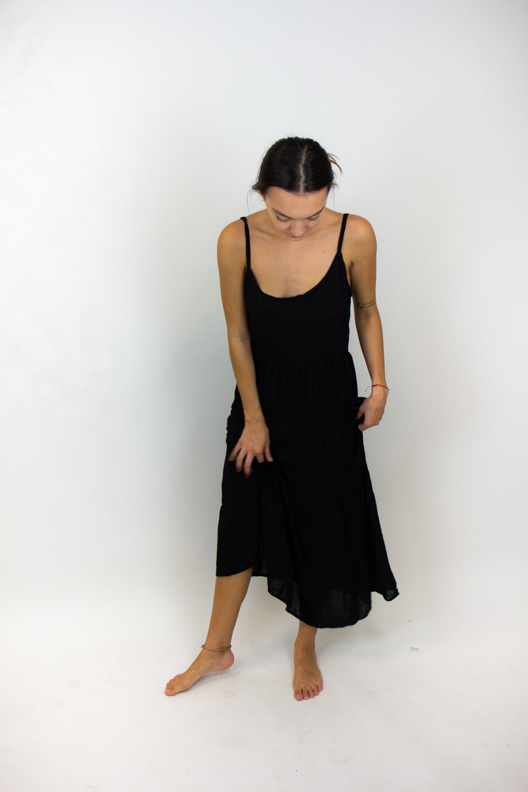This photo shows a long and lightweight dress that is black and spaghetti strapped. The model is twirling it to show how it moves.