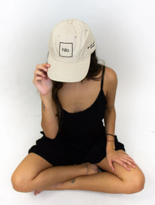 "The model in this photo is wearing a black outfit with a baseball cap that has the square ""Hilo"" logo on the front of it, embroidered in black thread."