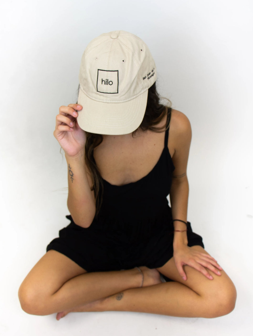 The model in this photo is wearing a black outfit with a baseball cap that has the square