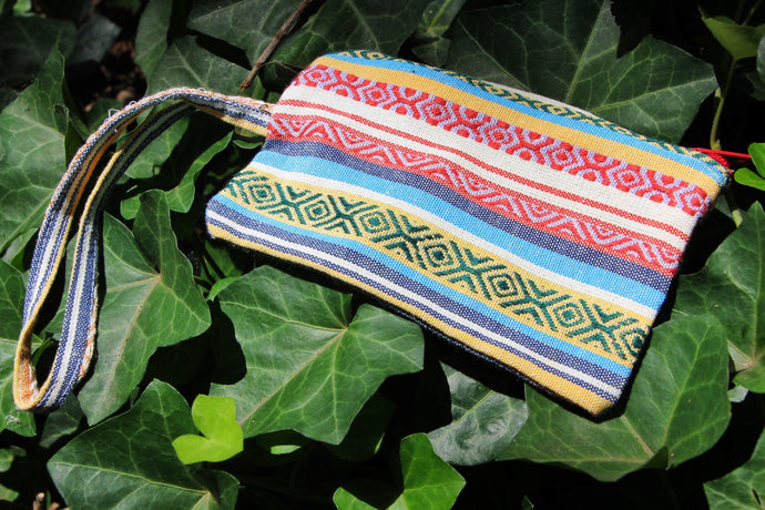 Photo shows a creme and pink and blue zip up pouch with a wrist strap attached.