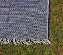 Load image into Gallery viewer, This shows the cotton blanket in a deep shade of navy, the deep blue is weaved with the same creme that the tassels that cover the shorter ends of this blanket.