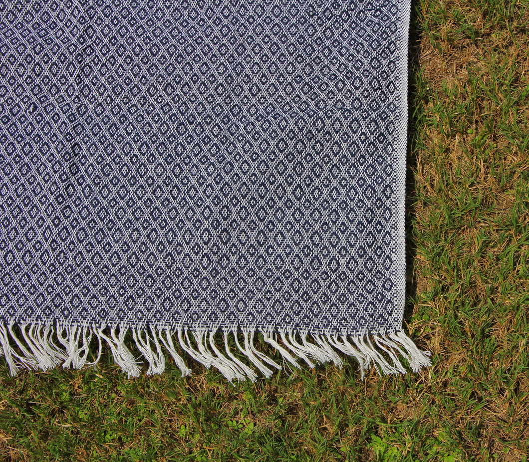 This shows the cotton blanket in a deep shade of navy, the deep blue is weaved with the same creme that the tassels that cover the shorter ends of this blanket.