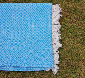 This photo shows a vibrant sky blue blanket folded and laying on green fluffy grass. There are creme colored tassels on the end and the cotton is weaved so there are small diamonds all over the blanket.