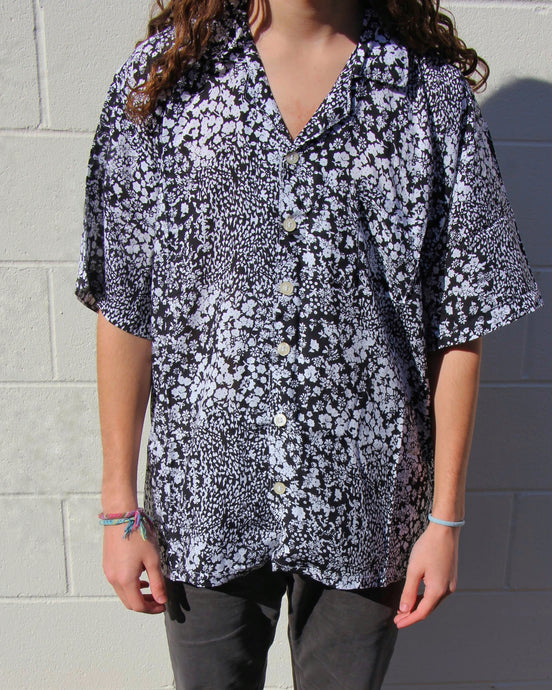 The model in this photo is wearing a black and white floral Men's button up shirt. The shirt is flowy on the model and has pearlescent buttons. The shirt has a free form and the loose fabric allows it to flow freely.