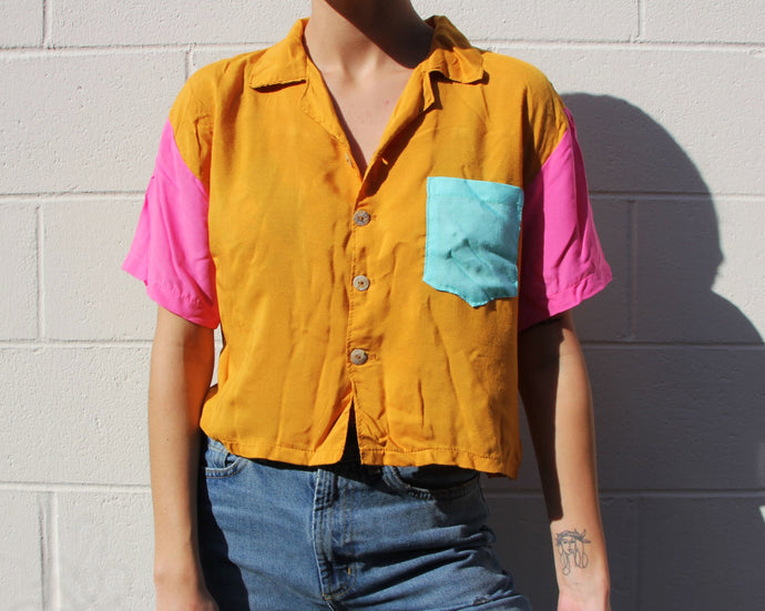 This photo is an up-close shot of a cropped button up shirt. The shirt has hot pink sleeves and a sky blue pocket, while the chest area of the shirt is a marigold orange color. This vibrant shirt has pearl shell buttons and is very flowy.