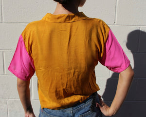 This photo shows the back of the shirt, the majority shirt being a marigold orange color, the sleeves are hot pink and hit just above the elbow.