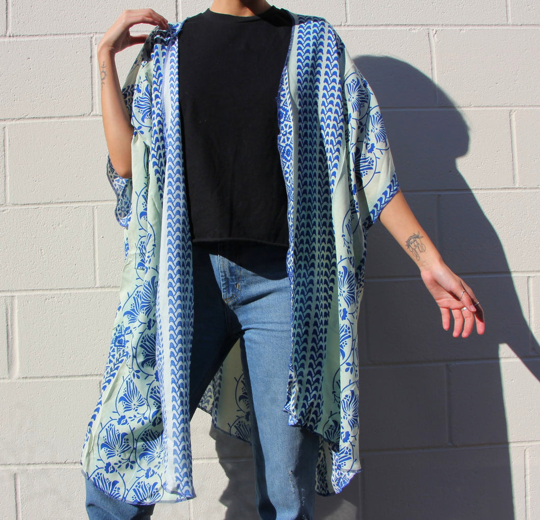This photo shows a model wearing a pair of jeans, a back t-shirt, and a very boxy and free flowing kimono. The kimono is white with a beautiful blue mediterranean pattern all over it, the pattern is large and in a Santorini blue color.
