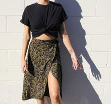 Load image into Gallery viewer, This photo a model wearing a wrap skirt that reaches just above the knees, and has a dark olive green and cheetah print. It sits high on the hips. The model wears it with a black T-shirt.