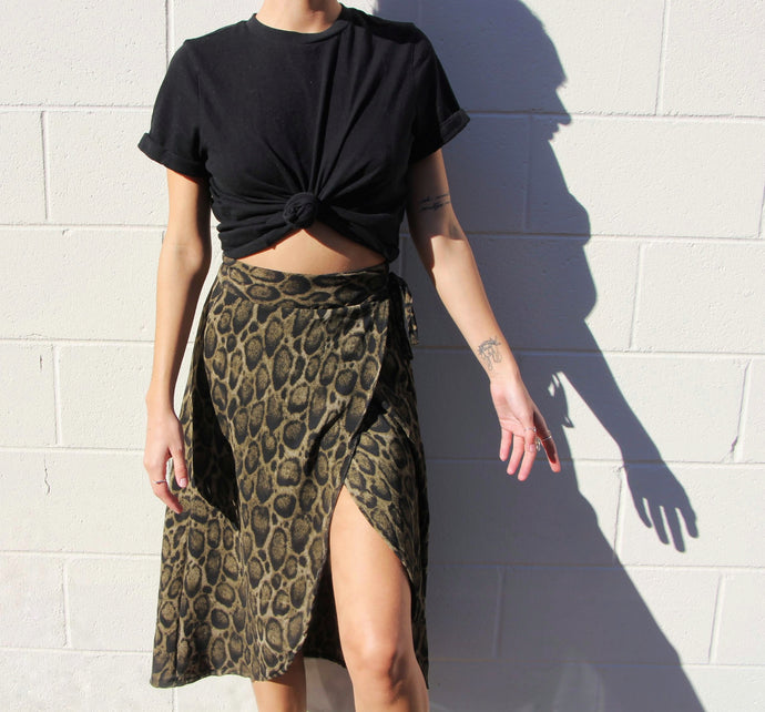 This photo a model wearing a wrap skirt that reaches just above the knees, and has a dark olive green and cheetah print. It sits high on the hips. The model wears it with a black T-shirt.