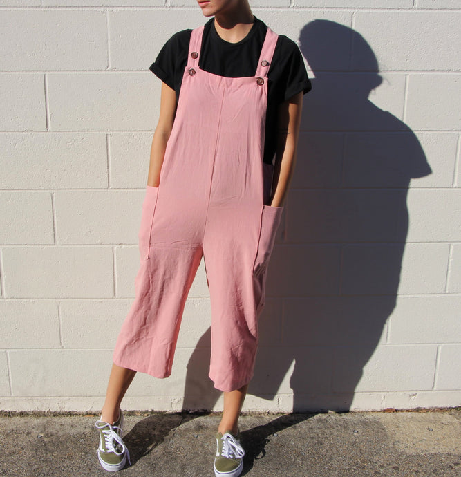 This is a photo of a girl wearing overalls, the photo does not show her face, just the outfit she's wearing. She is wearing a black t-shirt under the bubblegum pink colored overalls. The overalls' pants leg hits her mid-calf. the overalls have two straps on either shoulder that are used to adjust the length of the overalls. There are two large pockets on the low sides of the overalls where the model is resting her hands.