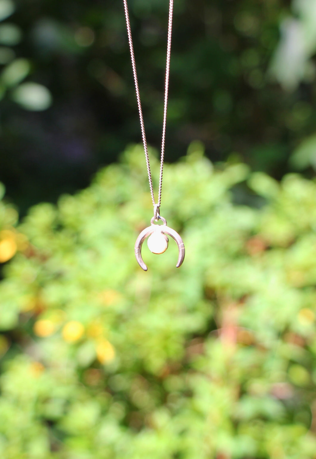 This photo shows a silver necklace with a pendant that is also silver in the shape of a moon, with a circular moonstone gemstone inside of the curve of the crescent moon.