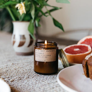 SWEET GRAPEFRUIT 7.2 OZ SOY CANDLE next to grapefruit