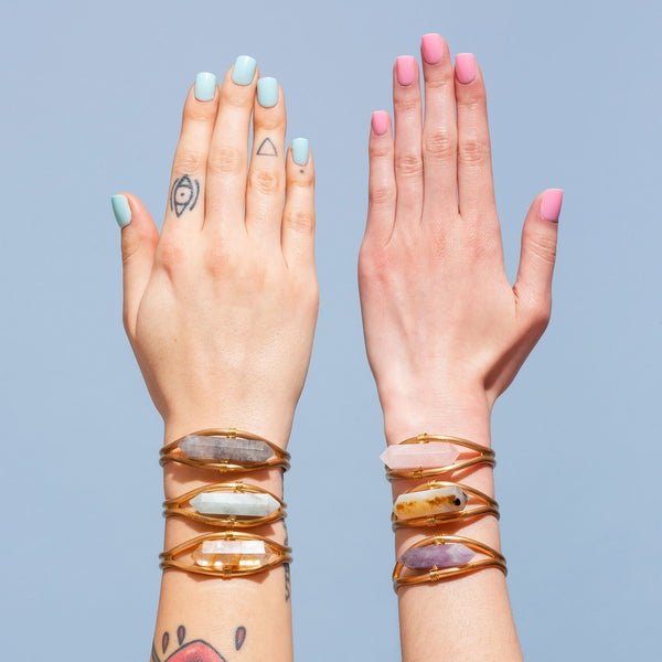 TWO HANDS WITH CRYSTAL BRACELETS
