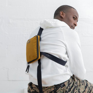 MAN WEARING SLINGSHOT CROSSBODY BAG | BRASS