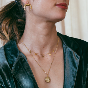 CLOSEUP WOMAN WEARING ZODIAC MEDALLION NECKLACE