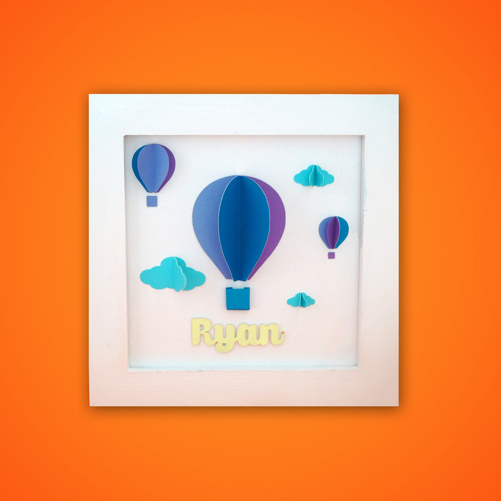 Ellybean Personalised Pop Up Frame, White wooden frame, three hot air balloons in dark blue, purple & mauve, light blue clouds, & gold name below.