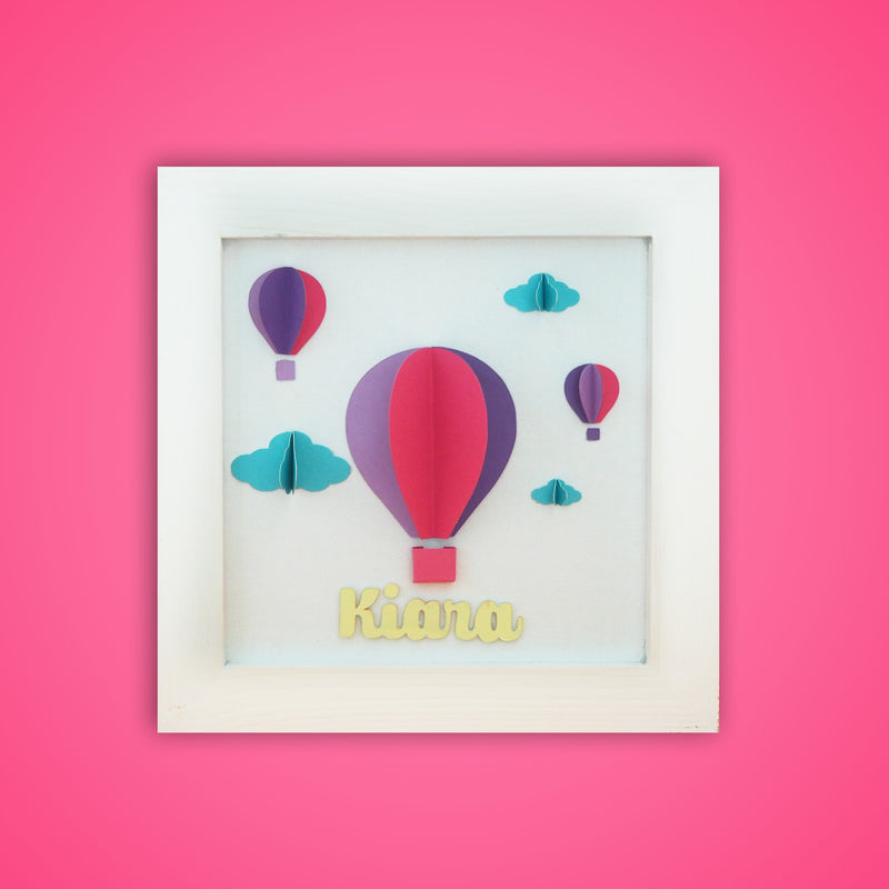 Ellybean Personalised Pop Up Frame, White wooden frame, three hot air balloons in fuschia pink, dark purple purple & lilac, light blue clouds, & gold name below.