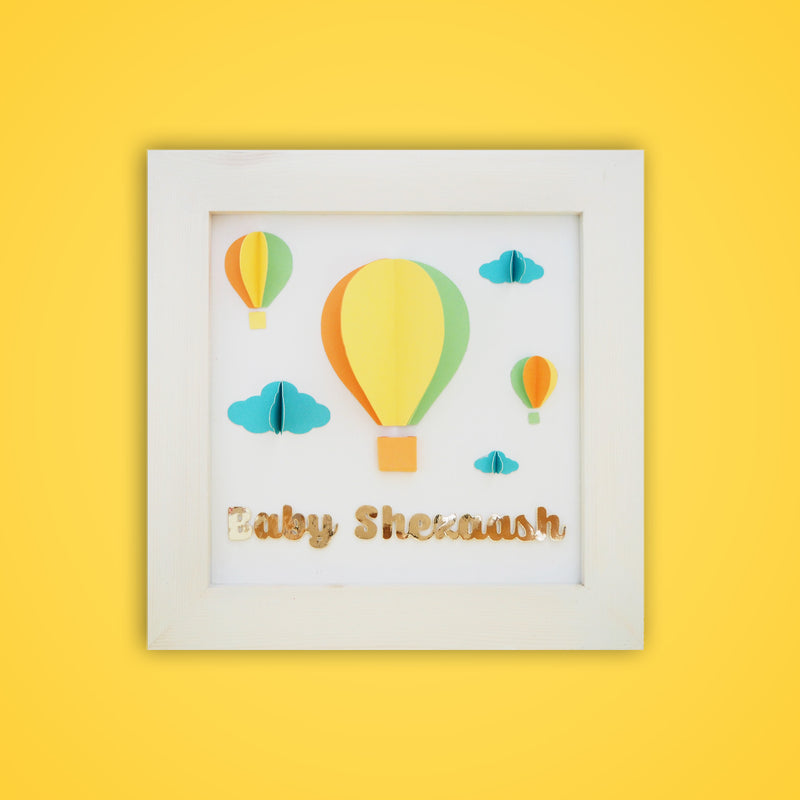 Ellybean Personalised Pop Up Frame, White wooden frame, three hot air balloons in lemon yellow, orange & pistachio green, light blue clouds, & gold name below.