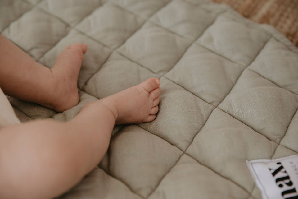 Baby laying on a quilted playmat in sage