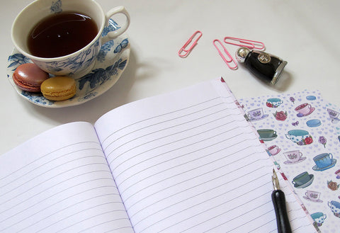 (Image) Notebook and stickers next to a teacup.