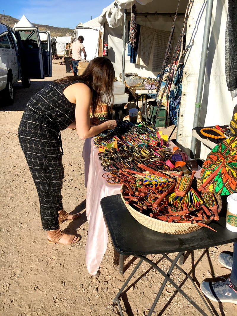 Suzy picking out colorful handcrafted goods for the betsy & iya Bazaar