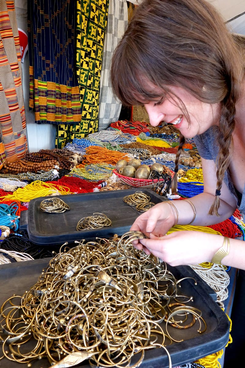 Designer Betsy Cross picking out handcrafted brass bracelets from Africa