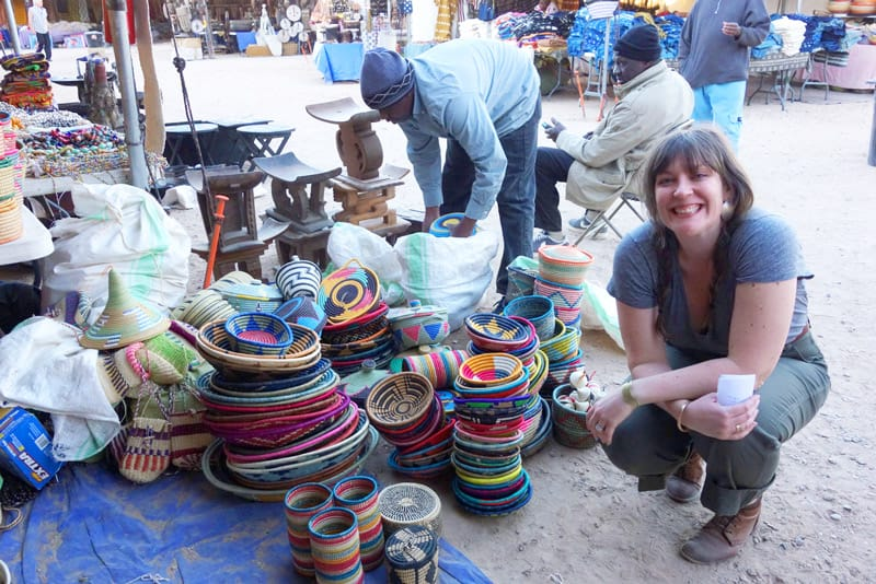 Designer Betsy Cross posing with colorful woven baskets