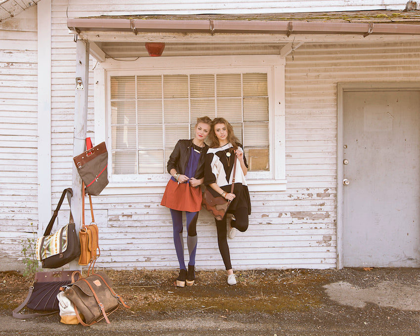 Two girls on a road trip standing outside of an abandoned building.