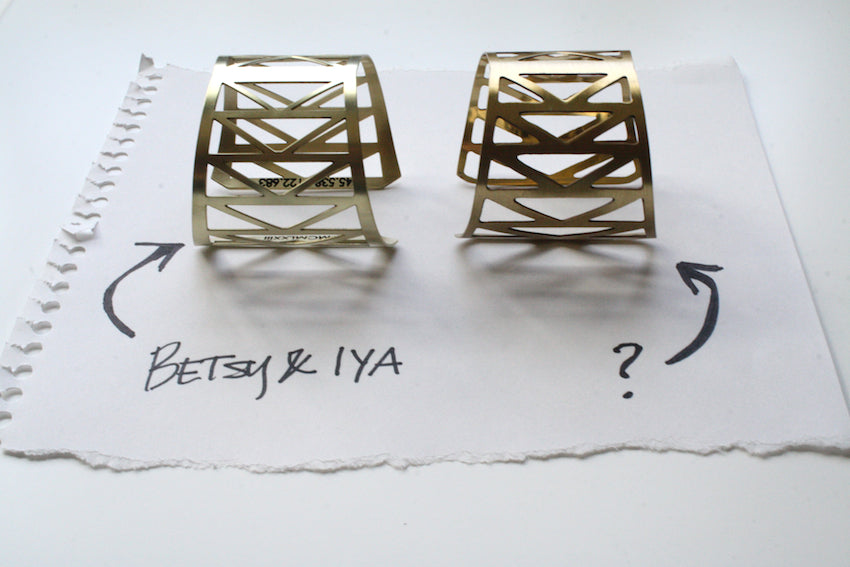 Two geometric cuff bracelets lay side by side, one designed and made by betsy & iya and the other we believe to be a copy of the original design.