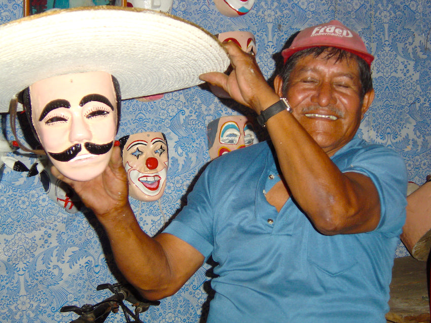 Mexican mask maker holding up a traditional Mexican mask.