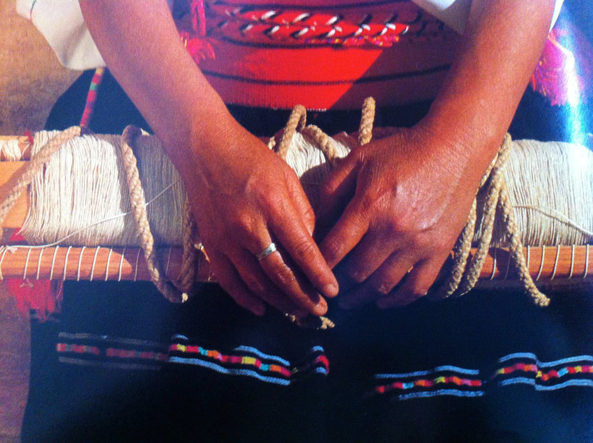 A Mexican weaver's hands lay on top of her colorful dress and weaving project.