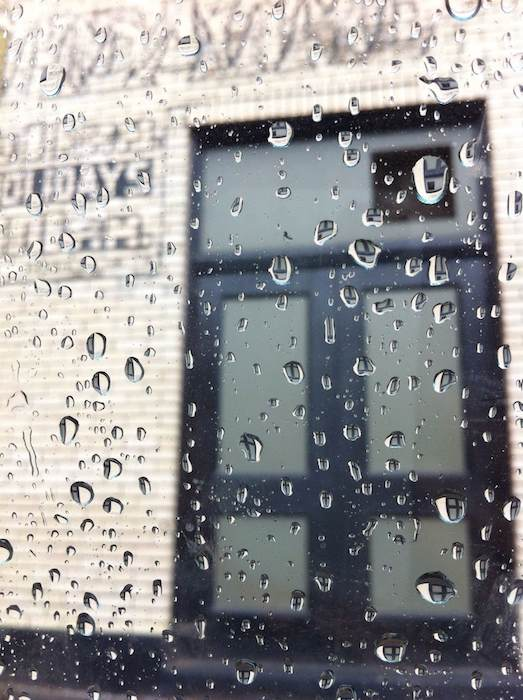 Raindrops on a window looking at a Portland building.