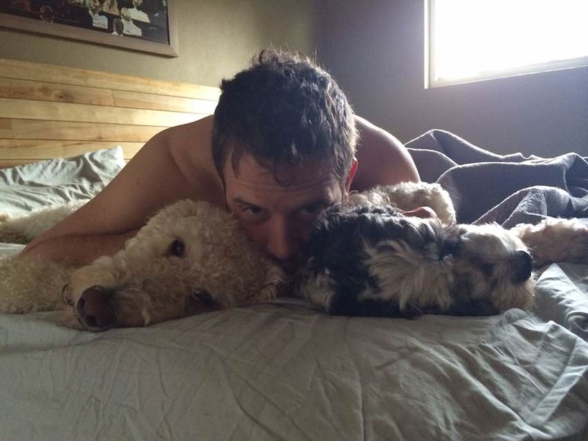 A handsome man and two dogs snuggle together on a bed.