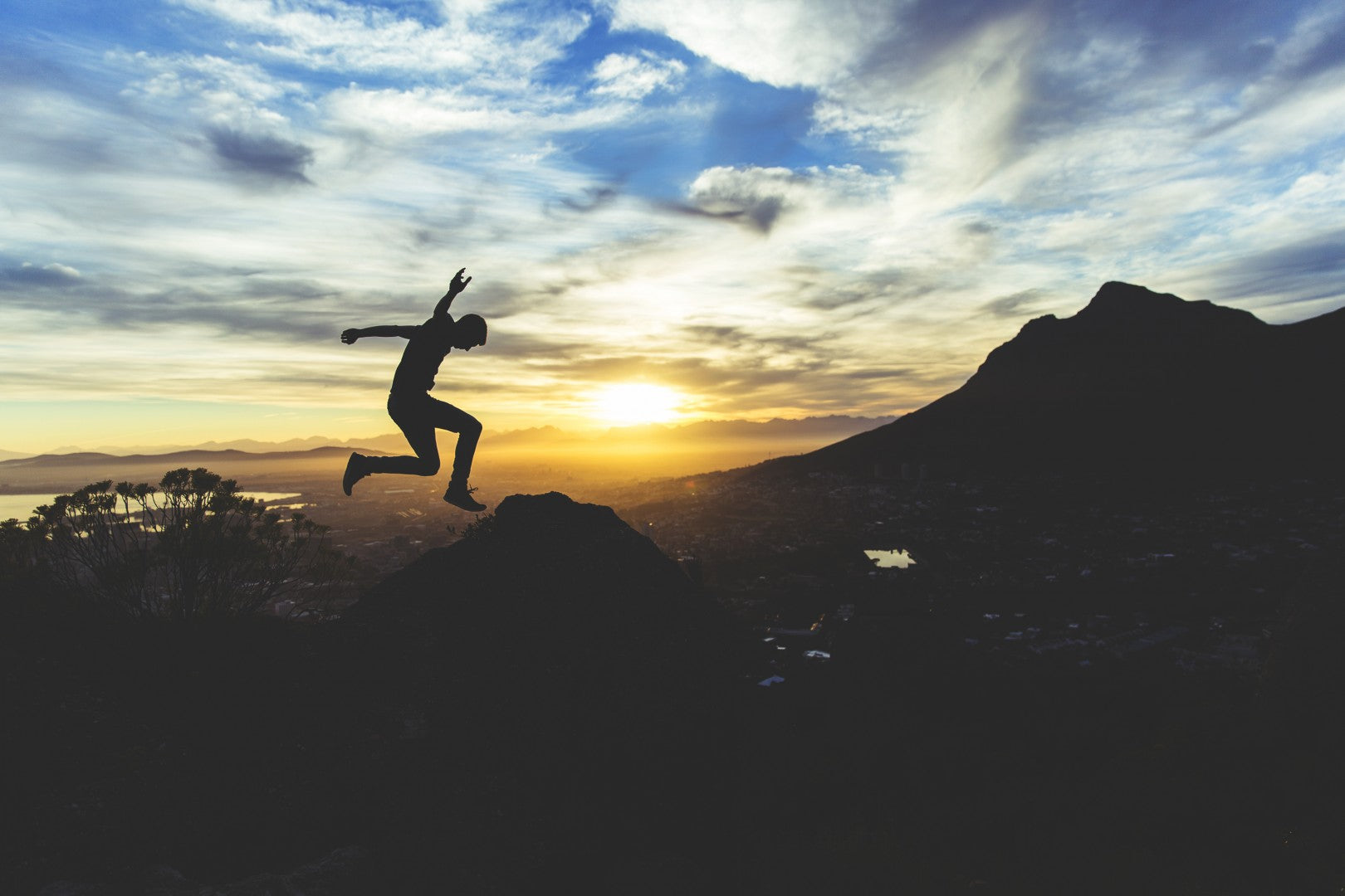 Sunset image of a person taking a big leap off of a cliff.