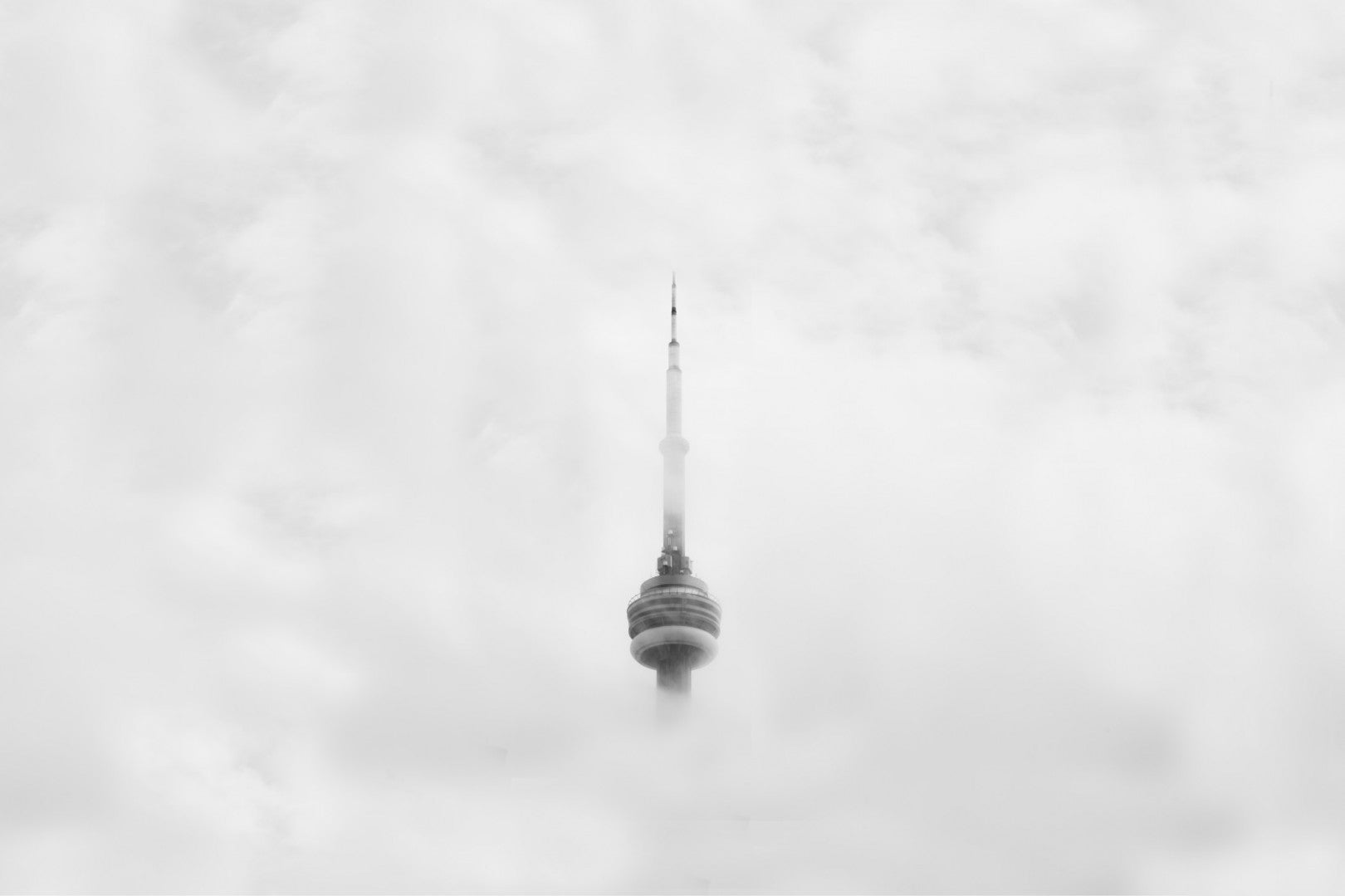 Cool tall tower and spire appear to be floating in the clouds in this black and white photo.