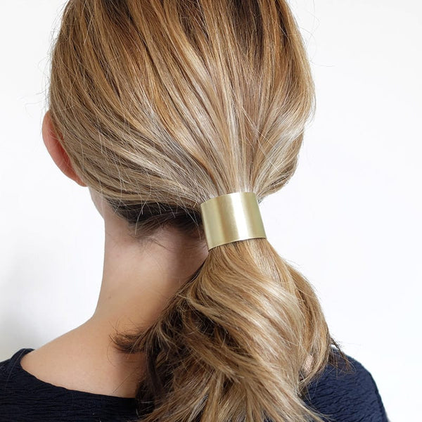 Curved metal ponytail holder in brass