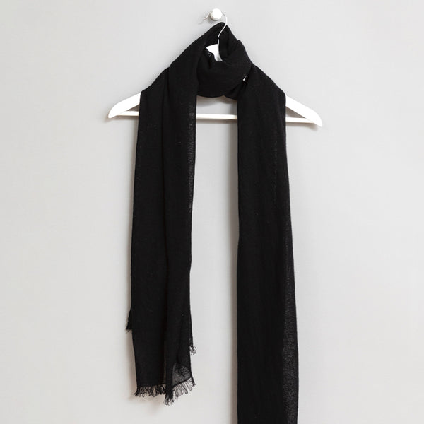 Black scarf wrapped around a white wooden hanger. The scarf has frayed edges. The Merino Woven Scarf in Black is from designer Dinadi.