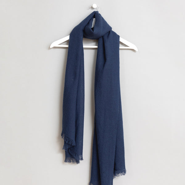 Blue scarf wrapped around a white wooden hanger. The scarf has frayed edges. The Merino Woven Scarf in Dark Blue is from designer Dinadi.